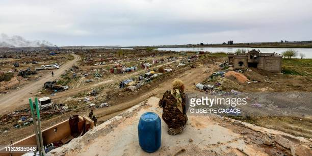 Member of the Syrian Democratic Forces sits next to a barrel atop a roof at a position in the village of Baghouz in Syria's eastern Deir Ezzor...