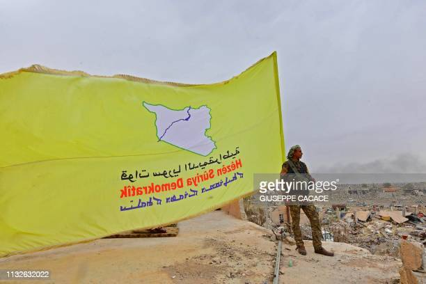 A member of the Syrian Democratic Forces stands next to the SDF's unfurled flag while on watch duty in the village of Baghouz in Syria's eastern Deir...