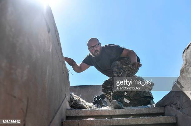 A member of the Syrian Democratic Forces takes cover during clashes with Islamic State group jihadists near the central hospital of Raqa on October 1...