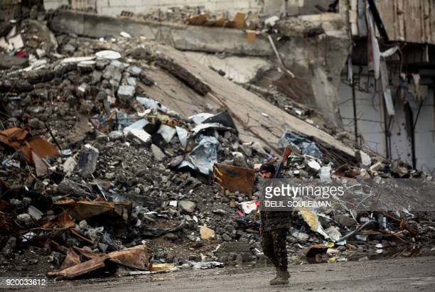 TOPSHOT A member of the Syrian Democratic Forces walks along a destroyed street in Raqa the former de facto capital of the Islamic State group on...