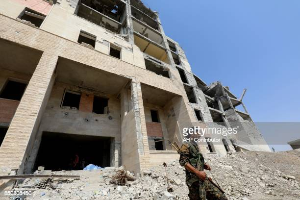 A member of the Syrian Democratic Forces walks in the former Islamic State stronghold of Raqa on September 21 2017 Syrian fighters backed by US...