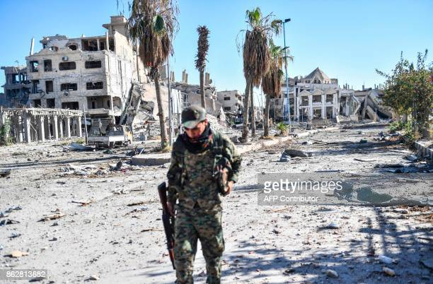 TOPSHOT A member of the Syrian Democratic Forces walks through a heavily damaged a street leading to an Armenian church in Raqa on October 18 2017...