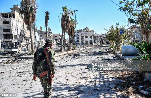 A member of the Syrian Democratic Forces walks through a heavily damaged a street leading to an Armenian church in Raqa on October 18 2017 The SDF...