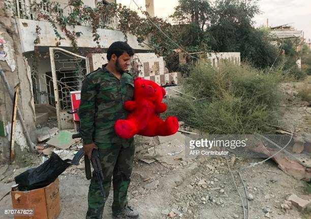 TOPSHOT A member of the Syrian government forces carries a teddy bear in a northeastern district of Deir Ezzor on November 5 after troops retook the...