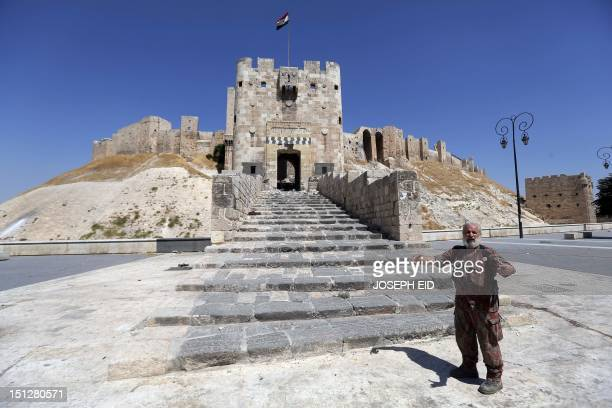 A member of the Syrian government forces gestures as he stands at the entrance of the Aleppo's historical citadel under the control of the Syrian...