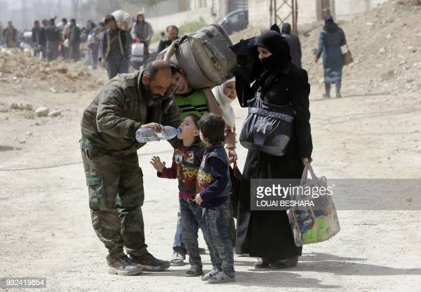 TOPSHOT A member of the Syrian government forces helps children drink from a water bottle during a civilian evacuation from the Eastern Ghouta...