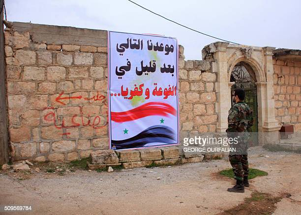 A member of the Syrian government forces looks at sign reading in Arabic Our next upcoming conquest Fuaa and Kafraya referring to the rebelbesieged...
