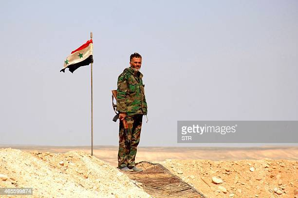 A member of the Syrian government forces stands at a look out point next to his national flag after they retook the village of Jihar and the...