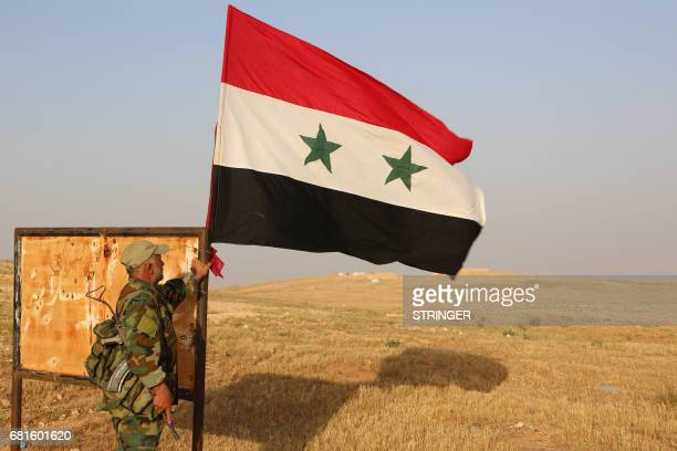 A member of the Syrian government forces stands next to a national flag as he secures a road for a military convoy in the desert area of Saba' Biyar...