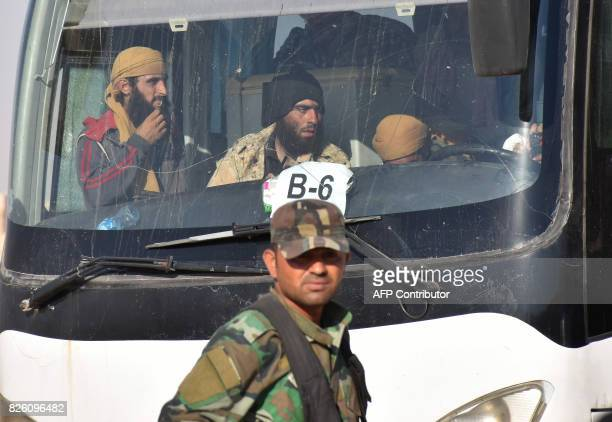 A member of the Syrian government forces walks past a bus transporting Syrian rebel fighters who were evacuated from Lebanon during an exchange...