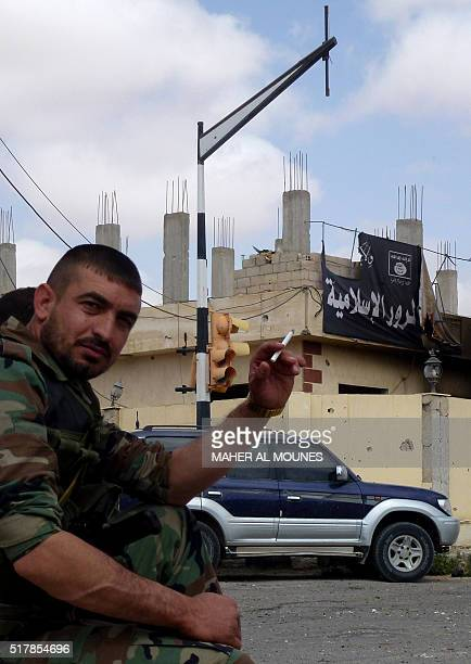 A member of the Syrian government troops smokes a cigarette near a banner bearing Islamic State group slogans in the damaged streets of the...