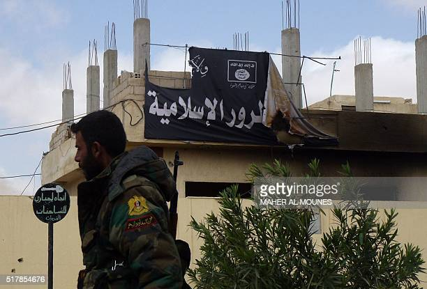 A member of the Syrian government troops walks past a banner bearing Islamic State group slogans in the damaged streets of the residential...
