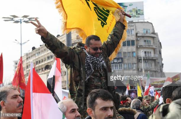 Member of the Syrian military waves a flag of Lebanon's Shiite Hezbollah movement in the central Saadallah al-Jabiri square in the northern Syrian...