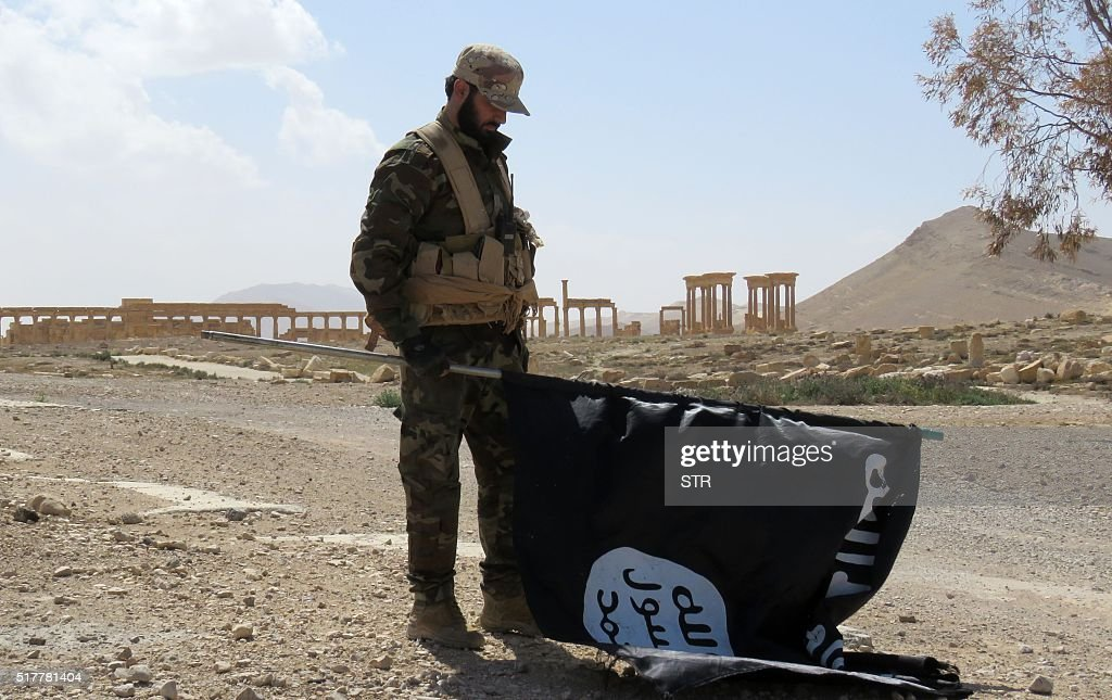 A member of the Syrian pro-government forces carries an Islamic State (IS) group flag as he stands on a street in the ancient city of Palmyra on March 27, 2016, after troops recaptured the city from IS jihadists. President Bashar al-Assad hailed the victory as an 'important achievement' as his Russian counterpart and key backer Vladimir Putin congratulated Damascus for retaking the UNESCO world heritage site. / AFP / STR