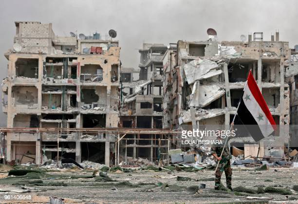 TOPSHOT A member of the Syrian progovernment forces carries the national flag as he stands in front of damaged buildings in the Yarmuk Palestinian...