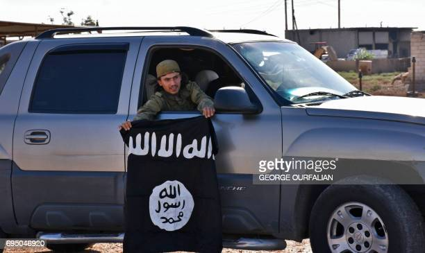 A member of the Syrian progovernment forces holds an Islamic State group flag after they entered the village of Dibsiafnan on the western outskirts...