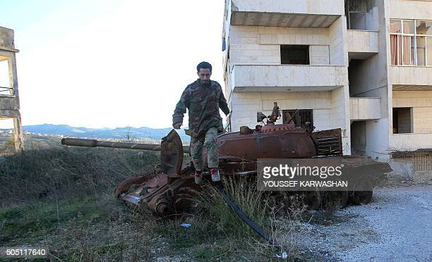A member of the Syrian progovernment forces jumps off a tank in the strategic town of Salma in the coastal Latakia province on January 15 following...