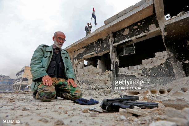 TOPSHOT A member of the Syrian progovernment forces prays in a destroyed street in the Hajar alAswad neighbourhood on the southern outskirts of the...