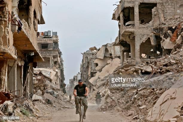 A member of the Syrian progovernment forces rides a bicycle through a damaged street in the Yarmuk Palestinian refugee camp on the southern outskirts...