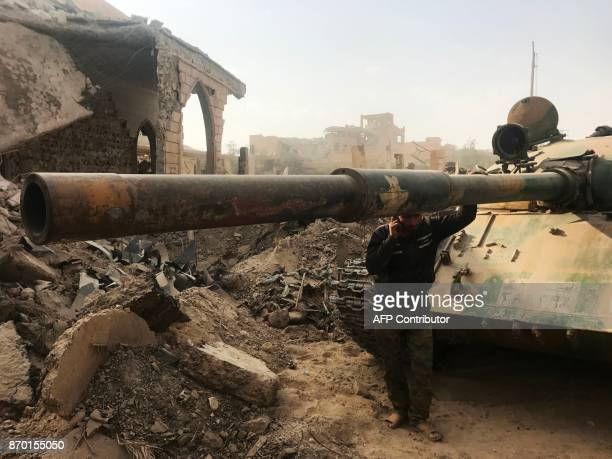 A member of the Syrian progovernment forces stands next to a tank in the eastern city of Deir Ezzor during an operation against Islamic State group...