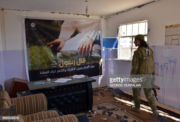 A member of the Syrian progovernment forces walks past a religious poster left by the Islamic State group in the village of Dibsiafnan on the western...