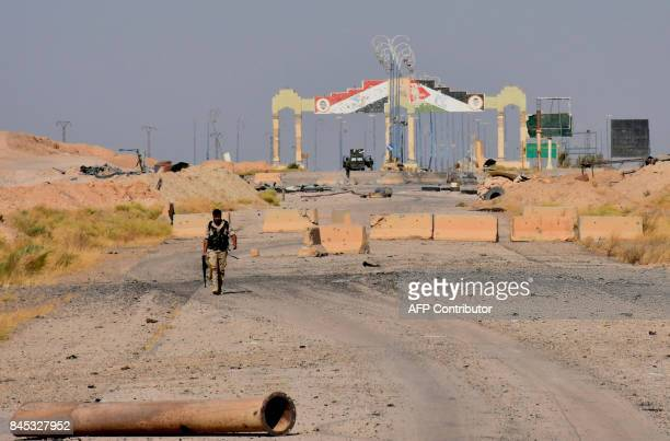 A member of the Syrian progovernment walks along a road on the outskirts of Deir Ezzor on September 10 as they continue to press forward with Russian...