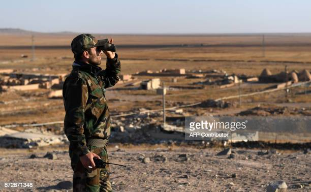 A member of the Syrian proregime forces looks through binoculars during the advance towards rebelheld positions west of Aleppo near Abu alZuhur...