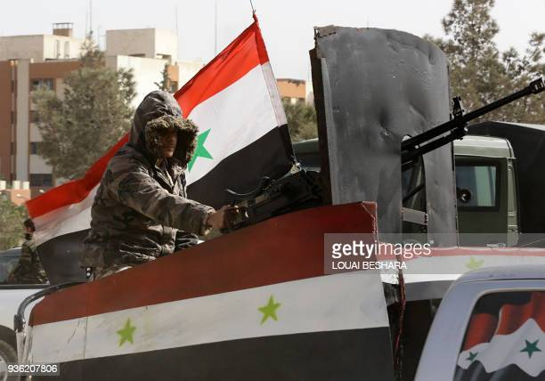 TOPSHOT A member of the Syrian regime forces sits in an armed vehicle at the entrance of Harasta in Eastern Ghouta on the outskirts of Damascus on...