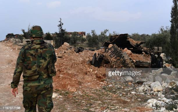 Member of the Syrian regime forces, walks past a destroyed tank on the outskirts of the town of Khan Tuman in the northern Syrian Aleppo province on...
