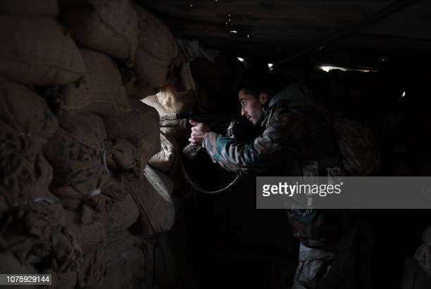A member of the Syrian regime forces watches through the opening of a sandbag barricade in the southern countryside of the northern Kurdishcontrolled...