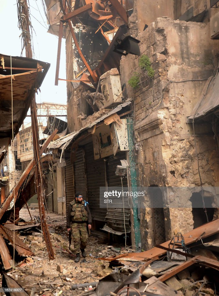 A member of the Syrian security forces inspects the heavily damaged Zahrawi souq during a patrol in the old city of Aleppo on February 23, 2013. The umbrella opposition National Coalition condemned world powers for failing to act to stop the slaughter in Syria, as missiles killed at least 29 in second city Aleppo.