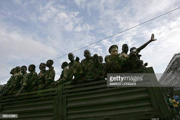 A member of the Tanzanian armed forces react towards a photographer as others aboard of an army truck celebrate the victory of the rulling...