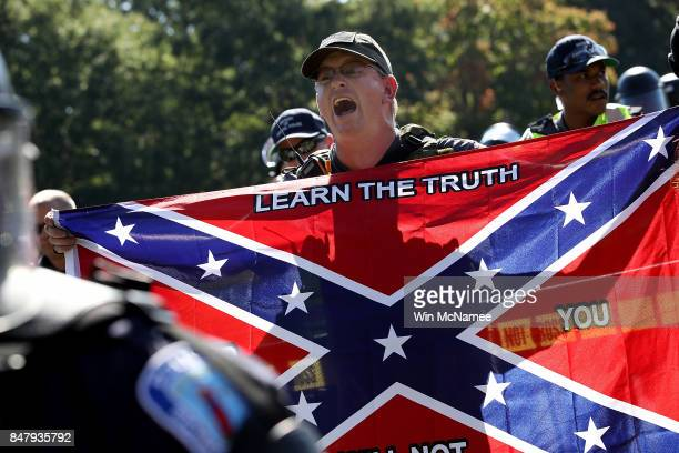 A member of the Tennessee based group New Confederate State of America yells at counter protesters while holding a confederate flag during a protest...