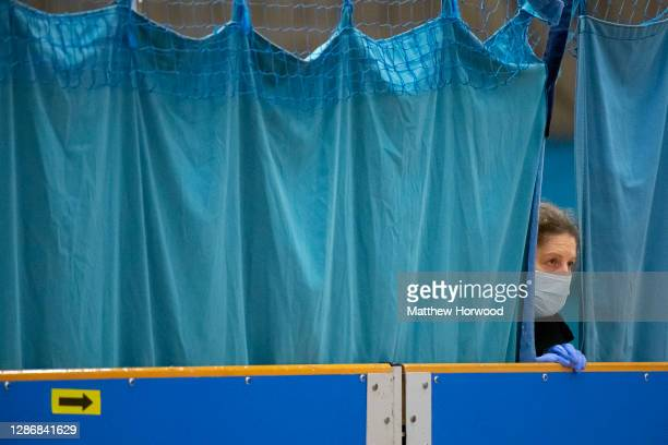 Member of the testing staff peers between curtains at Merthyr Tydfil Leisure Centre on November 21, 2020 in Merthyr Tydfil, Wales. From today anybody...