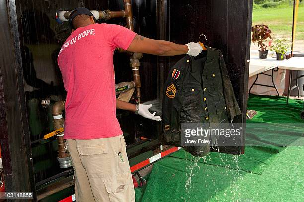 Member of the Tide's Loads Of Hope mobile laundry crew sprays off mud before he can put this soldier's uniform into one of the washing machines at...