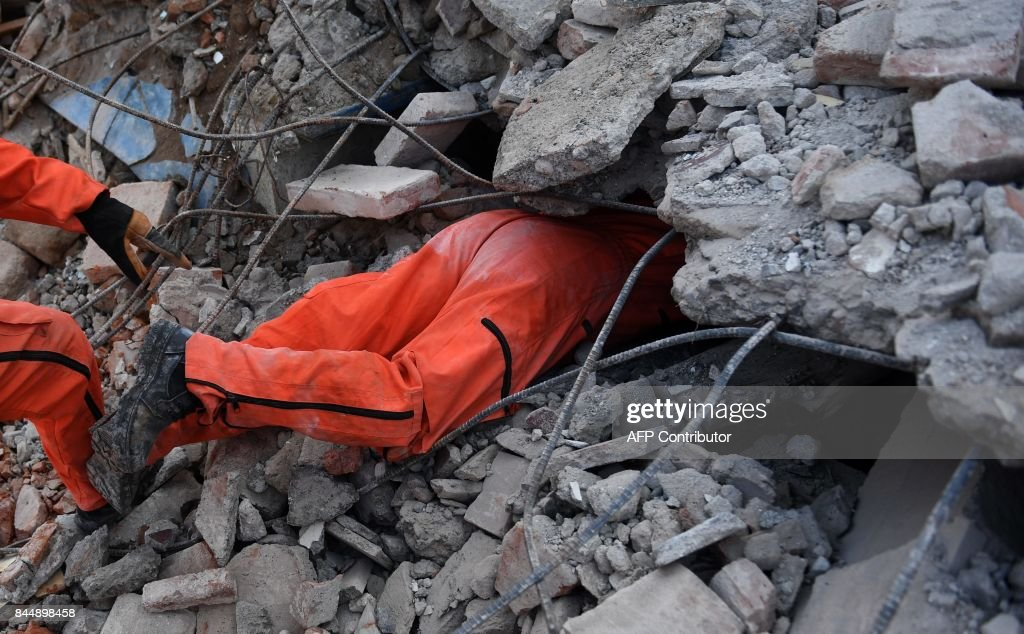 A member of the 'Topos' (Moles) specialized rescue team searches for survivors in Juchitan de Zaragoza, Mexico, on September 9, 2017 after a powerful earthquake struck Mexico's Pacific coast late on September 7. Police, soldiers and emergency workers raced to rescue survivors from the ruins of Mexico's most powerful earthquake in a century, which killed at least 61 people, as storm Katia menaced the country's eastern coast Saturday with heavy rains. / AFP PHOTO / Pedro PARDO