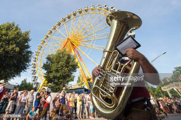 A member of the traditional costume parade 'Gaeubodenvolksfest' walks with a bass tuba through the innercity in Straubing Germany 08 August 2014 The...