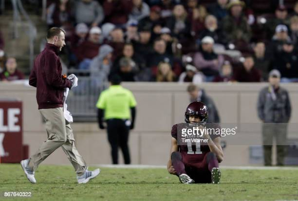 A member of the training staff tends to Kellen Mond of the Texas AM Aggies after an injury in the fourth quarter against the Mississippi State...