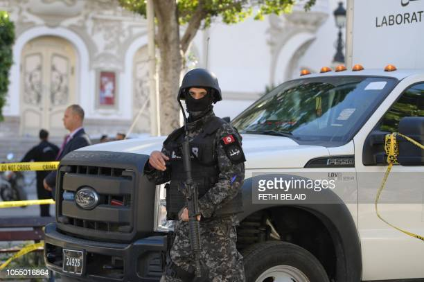 Member of the Tunisian security forces stands guard at the site of a suicide attack in the Tunisian capital Tunis on October 29, 2018. - A woman...
