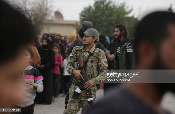 A member of the Turkeybacked forces looks on during the distribution of aid provided by the Turkish Red Crescent to displaced civilians on October 19...