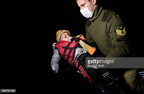 A member of the Turkish Coast Guard holds a child after Turkish Coast Guard rescued Syrian migrants aboard an inflatable dinghy attempting to reach...