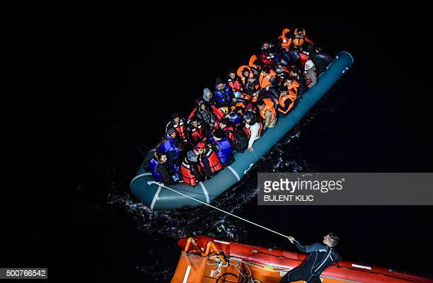 TOPSHOT A member of the Turkish Coast Guard pulls an inflatable dinghy transporting Syrian migrants attempting to reach the Greek island of Chios in...