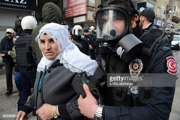 A member of the Turkish riot police detains a woman on January 17 after having disperse demonstrators protesting curfew in Sur district in the centre...