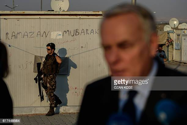 A member of the Turkish special police forces stands guard as French Foreign Minister JeanMarc Ayrault briefs the press during a visit to a refugee...