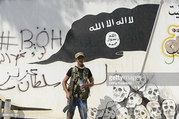 A member of the Turkishbacked Free Syrian Army stand guarded in front of a ISIS flag in the border town of Jarablus August 31 Syria Turkish troops...