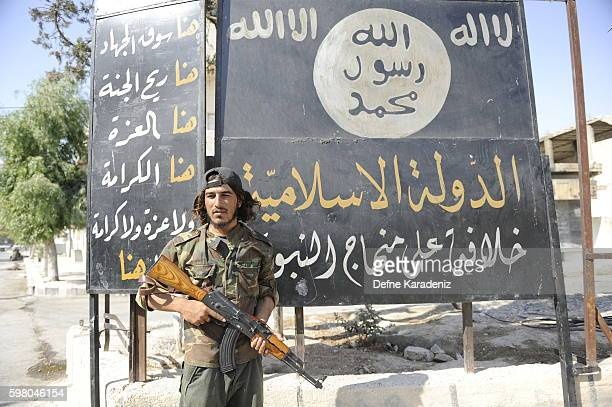 Member of the Turkish-backed Free Syrian Army stand guarded in front of a ISIS flag in the border town of Jarablus, August 31 Syria. Turkish troops...