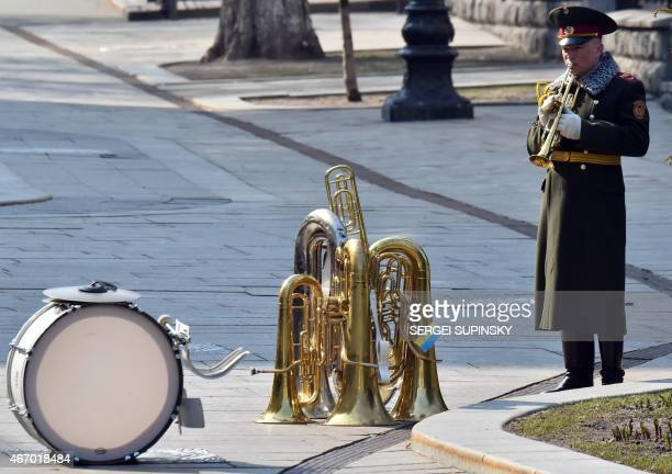 A member of the Ukrainian military band plays the trumpet as he waits for the start of a welcoming ceremony for the Turkish president in Kiev on...