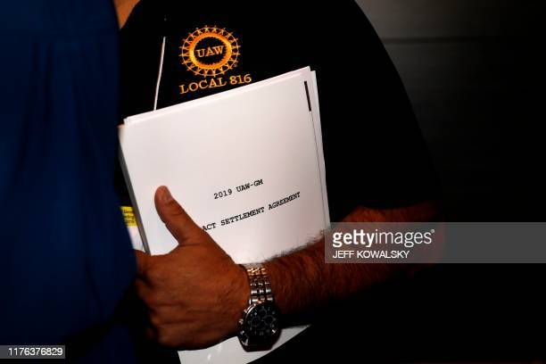 A member of the union carries a copy of the contract settlement agreement outside of the UAW GM Council Meeting held at the General Motors...