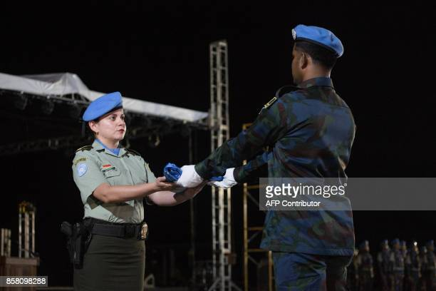 A member of the United Nations Stabilization Mission in Haiti hands the United Nations flag over a member of the Cameroon garrison part of the United...