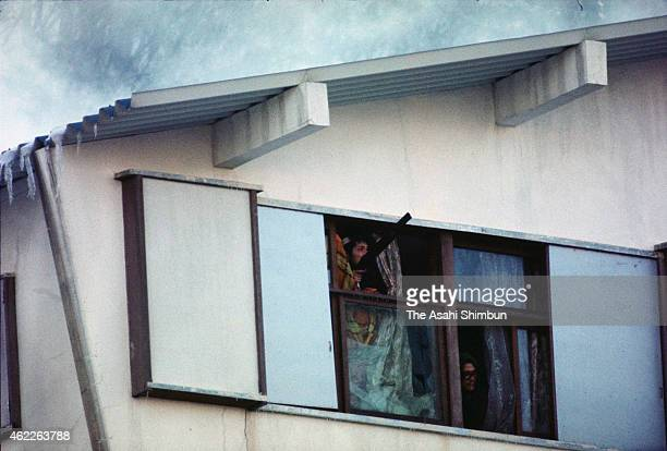 A member of the United Red Army looks out of the window as the police forces members to the corner with water and gas at the Asama Sanso holiday...